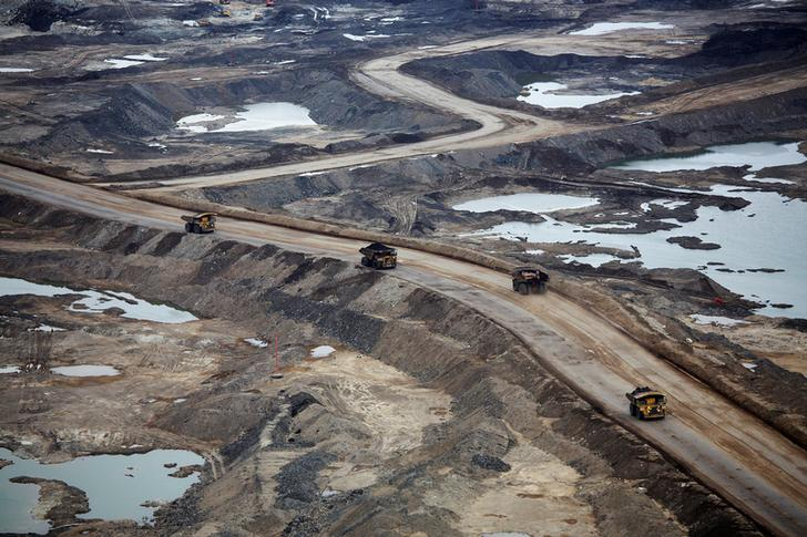 Giant dump trucks dump raw tar sands for processing at the Suncor tar sands mining operations near Fort McMurray