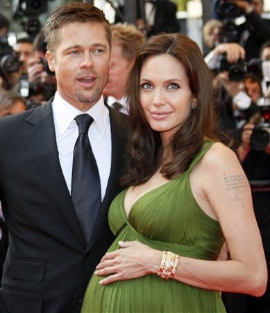 Uma gravidíssima Angelina Jolie acompanhada por Brad Pitt