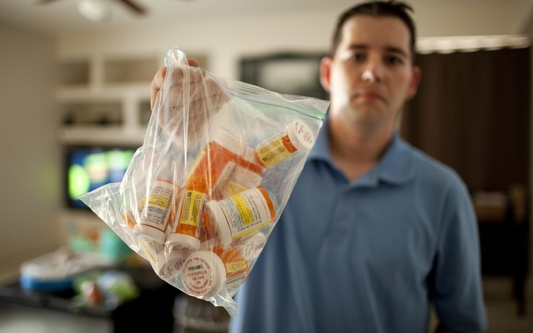 U.S. Army combat medic Shawn Aiken holds up the bag of his prescription medicines at his home in El Paso, Texas on May 20, 2013.    REUTERS/Ivan Pierre Aguirre