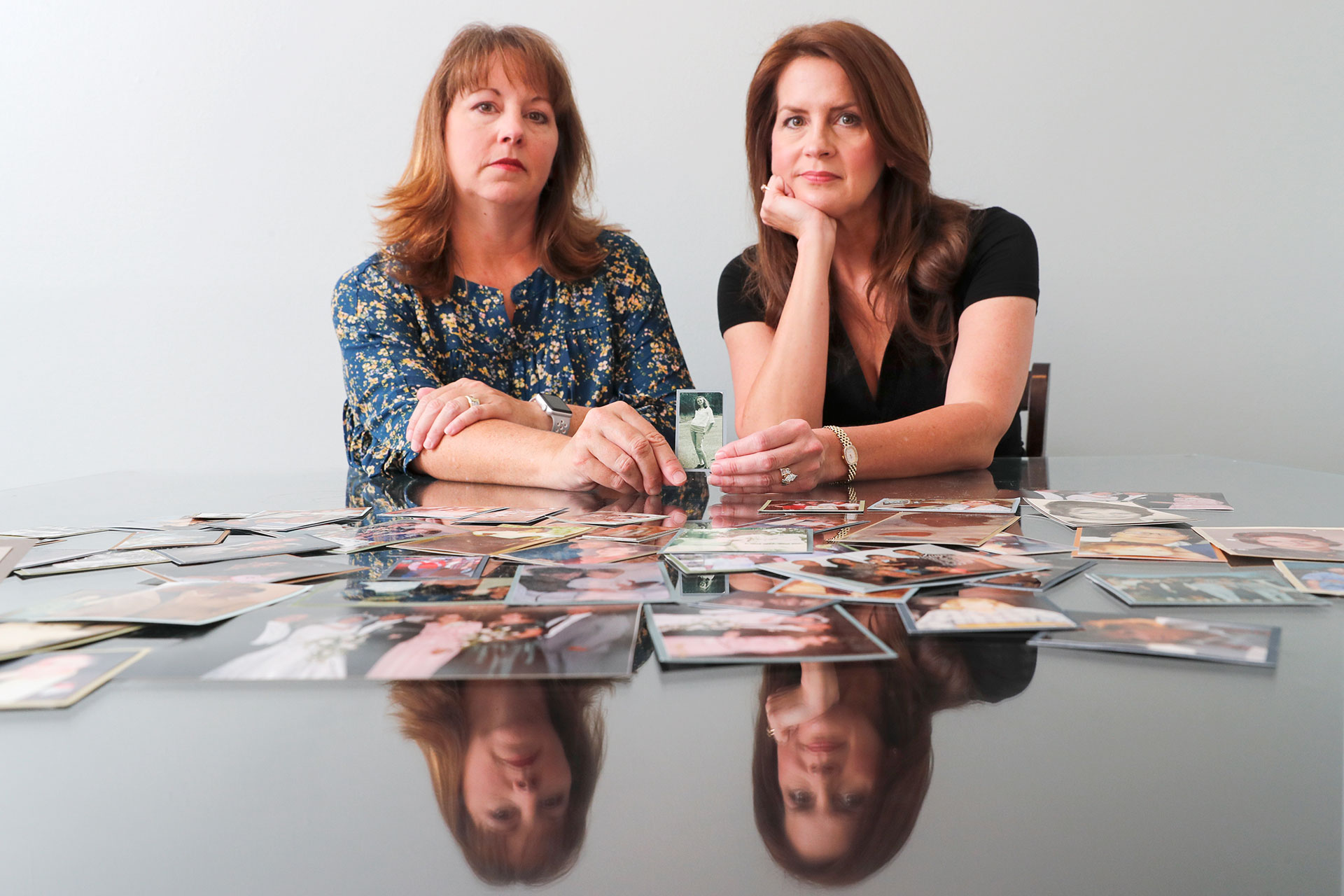 EARLY INDICATION: Cady Evans (left) and her sister, Crystal Deckard, surrounded by pictures of their mother, Darlene Coker, whose lawsuit against Johnson & Johnson 20 years ago was one of the first to allege that the company's Baby Powder caused cancer. REUTERS/Mike Blake