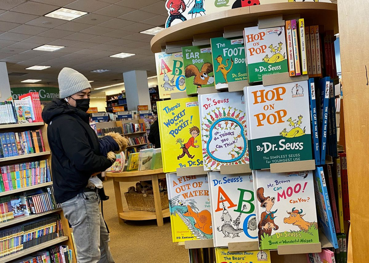 A shopper in a bookstore peruses a display of books by Dr. Seuss