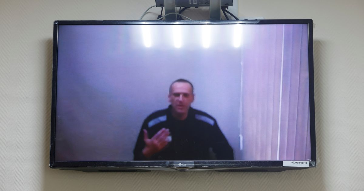 Russian opposition leader Alexei Navalny is seen on a screen via a video link during a hearing to consider his lawsuits against the penal colony over
