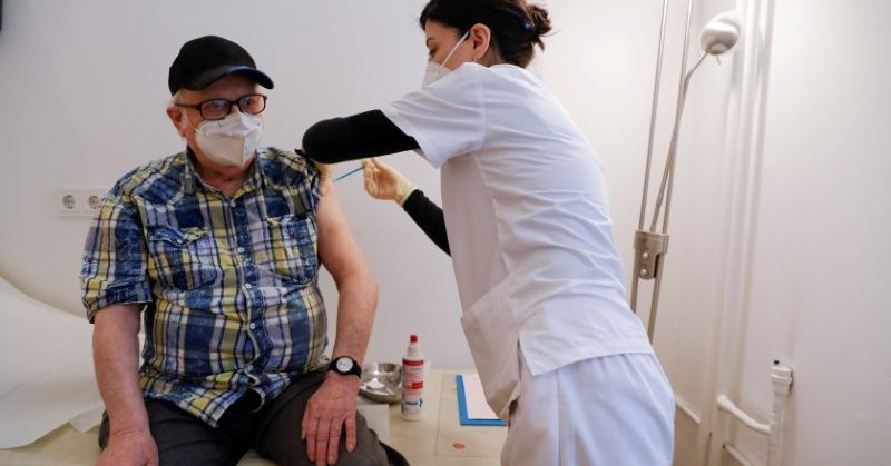 A doctor delivers the first dose of the Pfizer-BioNTech vaccine against the coronavirus to an 84-year-old man in Berlin, Germany, April 13, 2021. REUT