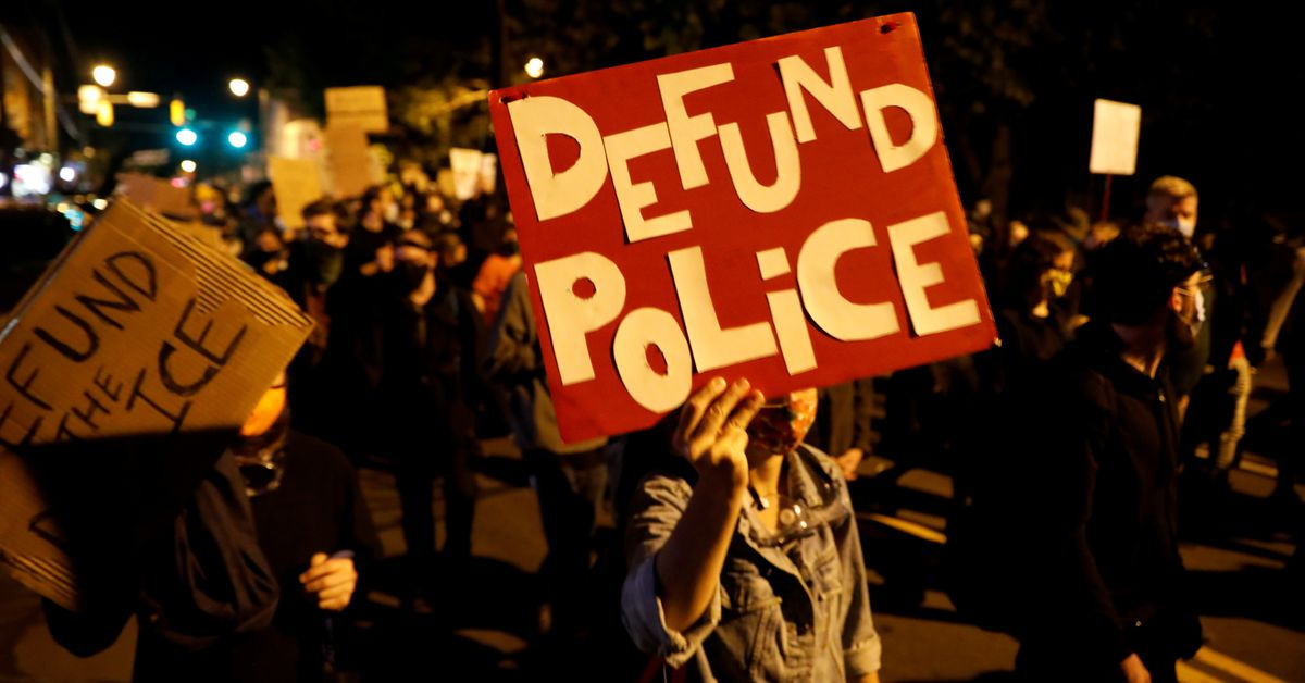 """Demonstrators hold a sign reading """"Defund the police"""" during a protest over the death of a Black man, Daniel Prude, after police put a spit"""
