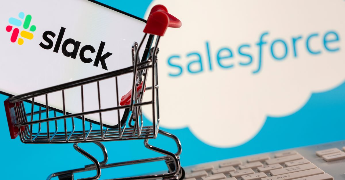 Smartphone with Slack logo stands in a shopping cart on a keyboard in front of displayed Salesforce logo in this picture illustration taken December 1