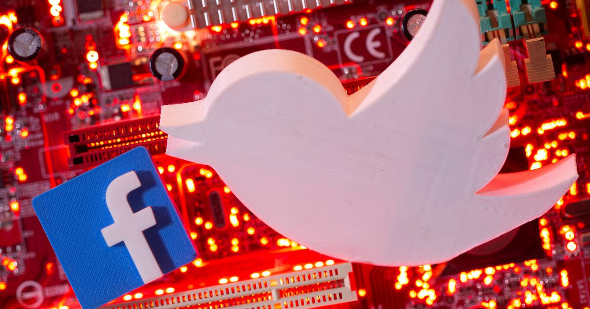 3D printed Facebook and Twitter logos are placed on a computer motherboard in this illustration taken Jan. 21, 2021. REUTERS/Dado Ruvic/Illustration A